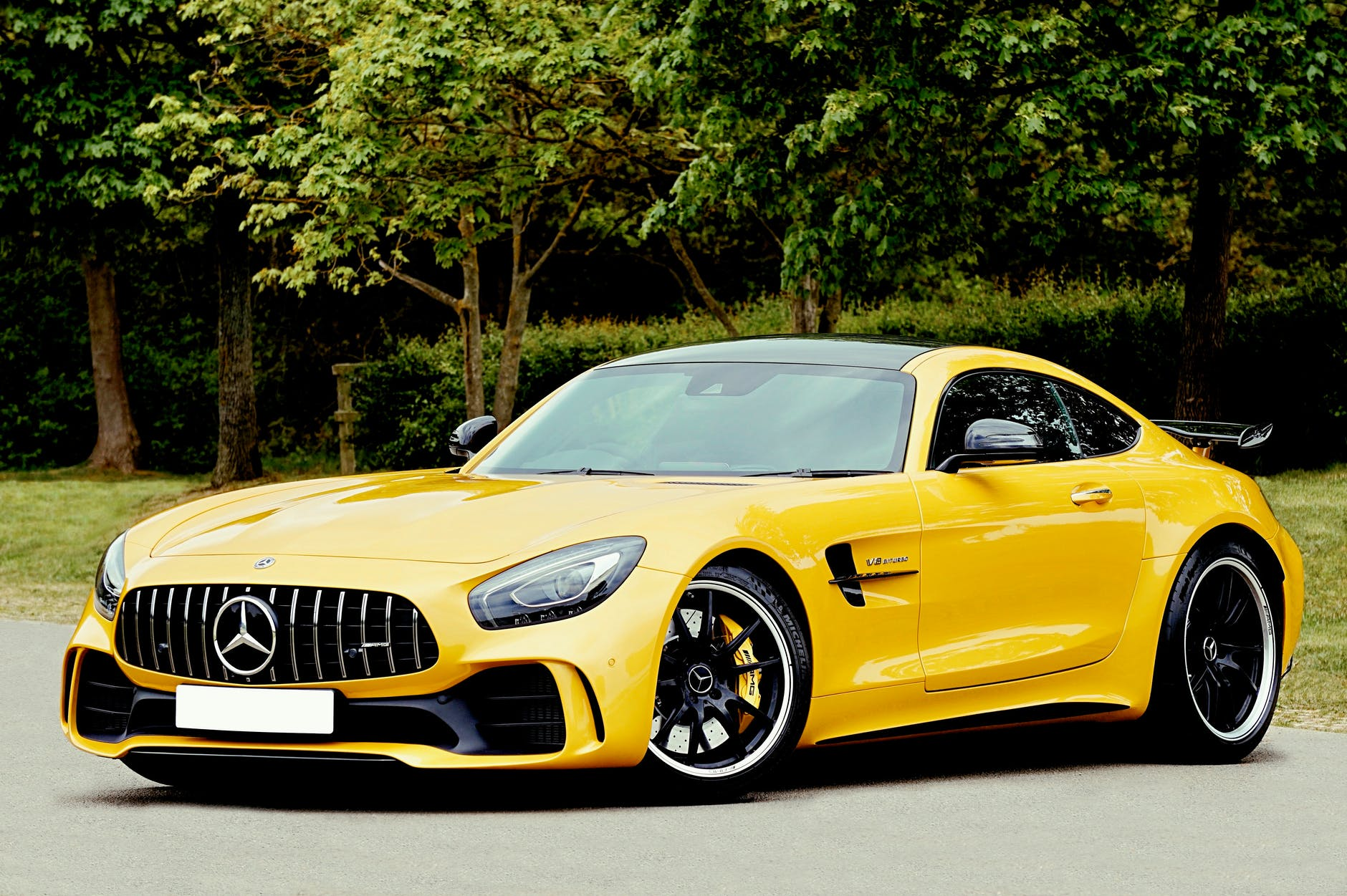 yellow mercedes benz beside trees